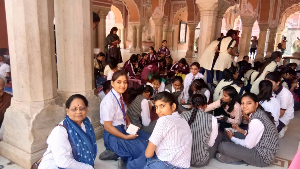 Ma'am sitting with children and guiding them